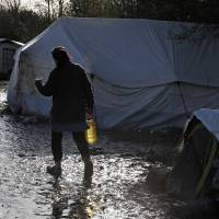 A migrant walks past shelters in a muddy field called the Grande-Synthe jungle, near Dunkirk, northern France, Tuesday. The Grande-Synthe jungle is a camp of tents and makeshift shelters where migrants and asylum seekers from Iraq, Kurdistan and Syria gather.   REUTERS