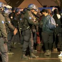 French gendarmes control migrants near the Grande-Synthe jungle of makeshift shelters, near Dunkirk, France, after three migrants were injured, one by gunshots, in what a charity worker said appeared to be a fight between rival bands of smugglers Tuesday. | REUTERS