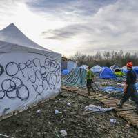Migrants walk in a muddy field at a camp of makeshift shelters for migrants and asylum-seekers from Iraq, Kurdistan, Iran and Syria, called the Grande Synthe jungle, near Dunkirk, France, Monday. | REUTERS