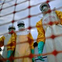 Doctors Without Borders staffers prepare to treat the body of an Ebola victim at their facility in Kailahun, Liberia, in August 2014. | AFP-JIJI