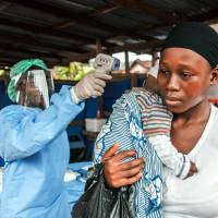 A woman has her temperature taken as part of Ebola prevention, prior to entering the Macauley government hospital in Freetown Thursday. A second case of Ebola emerged in Sierra Leone after health officials thought the epidemic was over, with a close relative of the first victim testing positive for the virus that has killed more than 11,000 people, authorities said Thursday. | AP