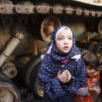 A girl attends Friday prayers on Feb. 18, 2011, in front of an army tank during the protests in Cairo's Tahrir Square. | REUTERS
