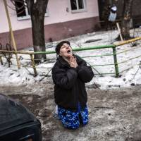 A woman begs Ukrainian President Petro Poroshenko to stop bombing the breakaway pro-Russian city of Donetsk after a shell hit the area where she lives, killing two civilians, last January. | AFP-JIJI