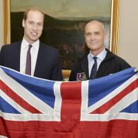 Britain's Prince William holds a Union Jack flag as he poses with explorer Henry Worsley at Kensington Palace in London, in October. Worsley, a British explorer who was trying to become the first person to cross Antarctica unsupported and unaided, has died after falling ill just 30 miles (50 km) short of completing his mission, his wife said Monday. | REUTERS