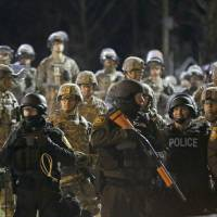 Police and Missouri National Guardsmen face protesters in front of the Ferguson Police Department on Nov. 28, 2014. | AP