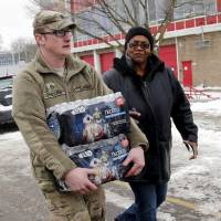 Michigan National Guard Staff Sgt. William Phillips assists a Flint resident with bottled water at a fire station on Wednesday. | REUTERS