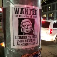 A mock wanted poster offering a $5,000 reward for the citizen's arrest of Michigan Gov. Rick Snyder is displayed in downtown Ann Arbor, Michigan, on Wednesday. The posters were among messages criticizing Snyder, including ones written in chalk on sidewalks, over his handling of the water crisis in Flint. | AP