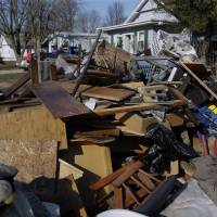 Residents pile ruined furniture, appliances and clothes along the street for disposal crews to pick up after last week's flooding from the south fork of the Sangamon River, Sunday in Kincaid, Illinois. | AP