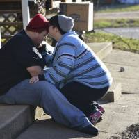 Jenn Bennett comforts her husband, Philip, outside their condemned trailer in Fenton, Missouri, on Saturday. | AFP-JIJI