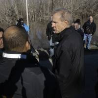 Illinois Gov. Bruce Rauner overlooks the south fork of the Sangamon River, where two teenagers were killed while crossing a flooded road last week, during his tour to the area Sunday in Kincaid, Illinois. | AP