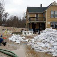 Dale Von Talge of Imperial monitors two water pumps pumping out water of a stressed street drain in Kimmswick, Missouri, Thursday. Floodwater was starting to recede at some hard-hit Midwestern communities Thursday, but hundreds of homes were damaged, hundreds more remained evacuated, and getting through St. Louis by car, boat or train was next to impossible. | LAURIE SKRIVAN / ST. LOUIS POST-DISPATCH VIA AP