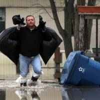 Keith Roeder leaves his trailer in the Starling Mobile Home Park with his clothing as the Meramec River continues to rise, in Arnold, Missouri, Thursday. Roeder, who was told to leave Wednesday night, said, 'I never ever though it would get this bad.' | LAURIE SKRIVAN / ST. LOUIS POST-DISPATCH VIA AP