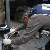 A police officer checks a bra found on a street near the flat of Ashley Olsen, a 35-year-old American expatriate artist who was found dead Saturday, during an investigation on Monday in the center Florence. | AFP-JIJI