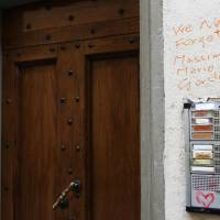 A picture taken on Jan. 1 shows messages and drawings on a wall at the entrance to the building that houses the flat of Ashley Olsen, a 35-year-old American expatriate artist who was found slain on Saturday, in Florence, Italy. | AFP-JIJI