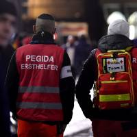 A first aid team is seen among protestors from the PEGIDA movement (Patriotic Europeans Against the Islamisation of the Occident) during a rally in Leipzig, Germany, on Monday. Supporters of the xenophobic far-right movement PEGIDA gathered to mark the first year of the local chapter LEGIDA, as public anger runs high over the Cologne assaults. | AFP-JIJI