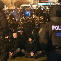 Riot police watch protestors from the PEGIDA movement (Patriotic Europeans Against the Islamisation of the Occident)stopped in the street before reaching a rally in Leipzig on Monday. | JAN WOITAS / DPA / AFP-JIJI