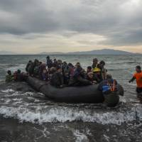 Volunteers assist refugees and migrants arriving on a beach after crossing a part of the Aegean sea from Turkey to the Greek island of Lesbos on Sunday. | AP