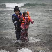 A man carries a child as they try to reach shore after falling into the sea while disembarking from a dinghy on which they crossed a part of the Aegean sea with other migrants, from Turkey to the Greek island of Lesbos, on Sunday. | AP