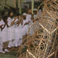 Guantanamo detainees pray before dawn near a fence of razor wire inside the Camp 4 detention facility at the Guantanamo Bay U.S. Naval Base on Cuba in this photo from May 14, 2009, reviewed by the U.S. military. | AP
