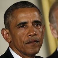 U.S. President Barack Obama is in tears while delivering a statement on steps the administration is taking to reduce gun violence, in the East Room of the White House in Washington Tuesday as Vice President Joe Biden looks on. | REUTERS