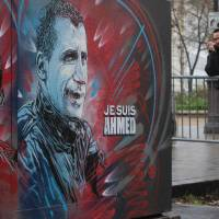 A painting with the message 'I am Ahmed' is seen in a street Tuesday after a ceremony to unveil a commemorative plaque at the site where policeman Ahmed Merabet was killed during the last year's January attack in Paris. | AFP-JIJI