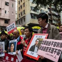As they walk toward the Chinese Liaison Office in Hong Kong on Sunday, protesters hold up missing person posters showing (from left to right) Mighty Current publisher Lui Bo and colleagues Cheung Jiping, Gui Minhai, Lee Bo and Lam Wing-kei. | AFP-JIJI
