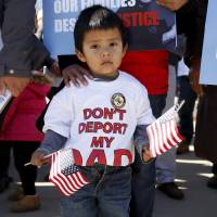 A young boy holds U.S. flags as immigrants and community leaders rally in front of the U.S. Supreme Court in Washington in November. The Supreme Court on Tuesday agreed to hear President Obama's bid to resurrect his plan to shield more than 4 million illegal immigrants from deportation, a unilateral executive action he took in 2014 to bypass the Republican-led Congress.   REUTERS