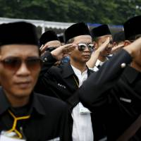 Young Muslim men salute Monday in Jakarta during a ceremony in support of the state against terrorism, radicalism and drugs. | REUTERS