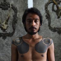 Agung Prasetyo, an Indonesian caretaker at the Bau Tanah tattoo museum in Jakarta, shows of his tattoo in October. The motif was inspired by Borneo's Dayak tribespeople. | AFP-JIJI