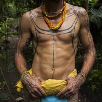 Australian filmmaker and tattoo artist Rob Henry, sporting tattoo designs originating from the Mentawai tribe, walks in the jungle during a traditional tattoo festival in the village of Maguwoharjo, Indonesia, last month. | AFP-JIJI