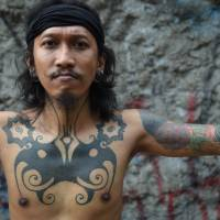 Ranu Khodir, a celebrated Jakarta tattoo artist who uses the traditional 'hand-tapping' method, displays his Dayak tribe motif tattoo at the Bau Tanah tattoo museum in Jakarta in October. | AFP-JIJI