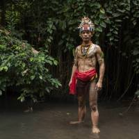 Esmat Sakulok, poses to display his body tattoo design, which originates from the Mentawai tribe, during a traditional tattoo festival in the village of Maguwoharjo, Indonesia, last month. | AFP-JIJI