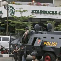 A police armored vehicle is parked outside a Starbucks cafe after an explosion in Jakarta on Jan. 14. | AP