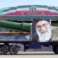 A military truck carrying a missile and a picture of Iran's Supreme Leader Ayatollah Ali Khamenei is seen during a parade marking the anniversary of the Iran-Iraq war (1980-88) in Tehran, in this Sept. 22 file photo. President Barack Obama's administration is preparing new sanctions on international companies and individuals over Iran's ballistic missile program. | FILES / TIMA / RAHEB / HOMAVAND / REUTERS