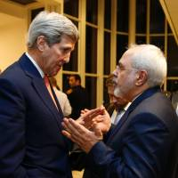U.S. Secretary of State John Kerry speaks with Iranian Foreign Minister Mohammad Javad Zarif after the International Atomic Energy Agency verified that Iran has met all conditions under the nuclear deal during the E3/EU+3 and Iran talks in Vienna on Saturday. | AFP-JIJI