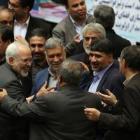 Members of the Iranian parliament greet Foreign Minister Mohammad Javad Zarif (left) in Tehran on Jan. 17, after sanctions were lifted under Iran's nuclear deal with world powers. | AFP-JIJI