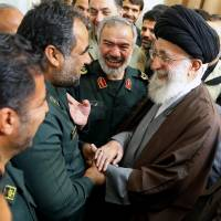 Iran Supreme Leader Ayatollah Ali Khamenei greets a group of Revolutionary Guard officers in Tehran on Sunday. The officers were involved in the detention of U.S. Navy sailors earlier this month. | AFP-JIJI