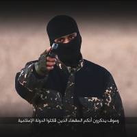 A masked man points a weapon as he speaks in this still image from an Islamic State execution video obtained Monday. | REUTERS