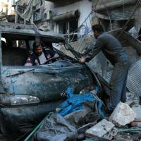 Syrian men inspect a damaged vehicle in the rubble following a reported airstrike by Syrian government forces on the Sukkari neighborhood of Syria's northern city of Aleppo on Saturday. | AFP-JIJI