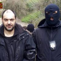 A police officer escorts mob fugitive Giuseppe Ferraro in this picture released Friday. Italian police arrested two fugitive mobsters in a bunker built on a steep slope and surrounded by dense brush where they had been hiding for years to avoid prosecution for mafia association, extortion and murder. | REUTERS