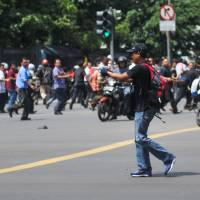 People run as an unidentified man with a gun walks on Thamrin street near the Sarinah shopping mall in Jakarta on Thursday. | AP