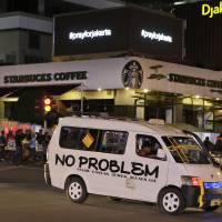 An electronic screen above the Starbucks cafe where an attack took place displays the message 'Pray for Jakarta' showing support for the city in Jakarta Thursday. Attackers set off bombs and exchanged gunfire outside the cafe in Indonesia's capital in a brazen assault Thursday that police said 'imitated' the recent Paris attacks. | AP