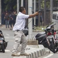 A plainclothes police officer aims his gun at attackers during a gun battle following explosions in Jakarta Thursday. | AP