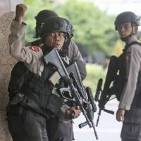 A police officer signals to a squad mate as they search a building following an explosion during a terrorist attack on Jakarta on Thursday. | AP