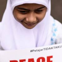 An Indonesian schoolgirl holds a placard during a gathering in Jakarta on Friday, a day after the capital was hit by coordinated terrorist attacks. | AFP-JIJI