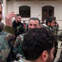 Forces loyal to the Syrian regime celebrate on a street after Syria's army and allied forces took full control from rebel groups of the strategic town of Salma, Syria, Tuesday. | AFP-JIJI