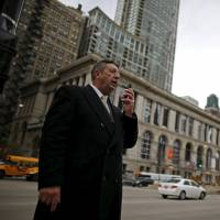 U.S. Republican presidential candidate Michael Petyo leaves a voice message while campaigning in downtown Chicago last November. | REUTERS
