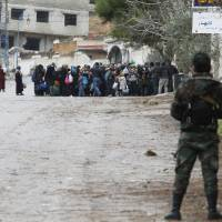 Syrian Army soldiers monitor residents who said they have received permission from the Syrian government to leave the besieged town as they wait with their belongings after an aid convoy entered Madaya, Syria, Thursday. Aid was sent on Thursday to the Syrian town blockaded by pro-government forces and two villages besieged by rebels for the second time this week, and a U.N. official said he hoped to make more deliveries to areas where people are starving. | REUTERS