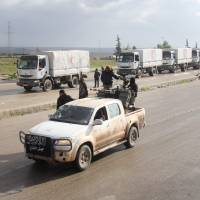 A vehicle belonging to Jaish al-Fatah (Army of Conquest) drives along convoys from the Syrian Arab Red Crescent carrying aid for the besieged towns of Fuaa and Kafraya, in Syria's northwest Idlib province, on Thursday. A spokesman for the International Committee of the Red Cross said that a convoy of 44 aid trucks was travelling from Damascus to Madaya, while a separate convoy of 17 trucks left the capital for Fuaa and Kafraya, two towns in Syria's northwest encircled by rebels. | AFP-JIJI