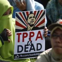 A Malaysian protester poses for a photograph holding an anti-Trans-Pacific Partnership agreement placard with U.S. President Barack Obama's caricature during a protest in Kuala Lumpur on Saturday. | AP